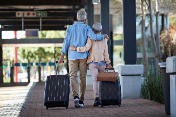 Couple de seniors à l'aéroport en vue d'un voyage de tour du monde