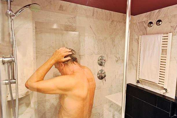 Personne âgée qui prend sa douche dans une salle de bain adaptée aux seniors