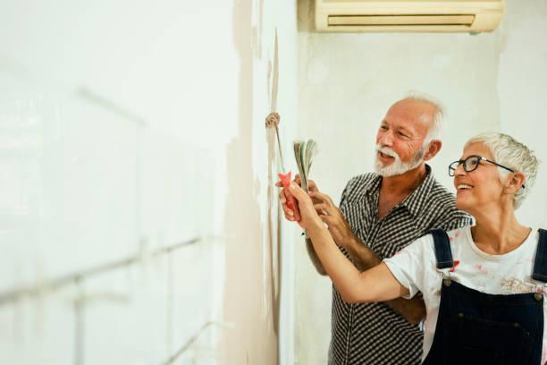 Couple de personnes âgées en train de peindre un mur