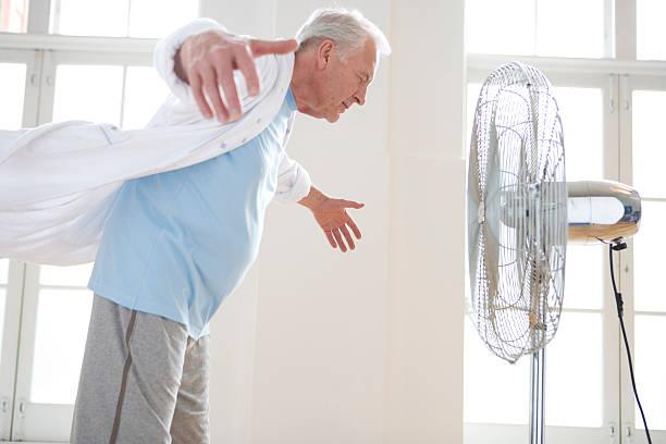 Retraité en train de se rafraichir face à un ventilateur