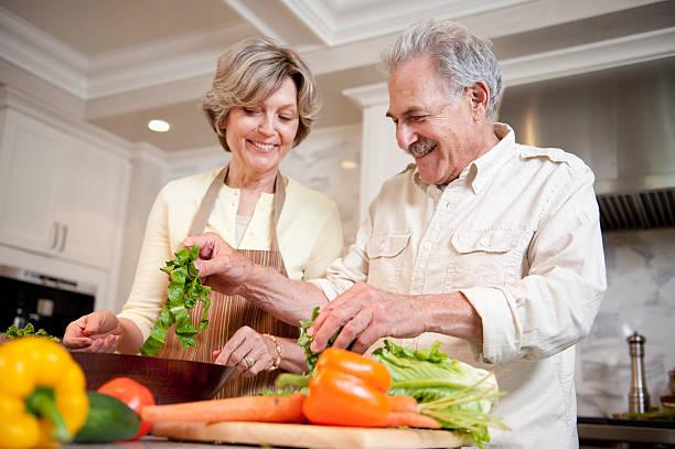 Couple de retraités en train de cuisiner une salade de légumes froids