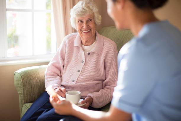 Auxiliaire de vie qui prend le thé avec une personne âgée