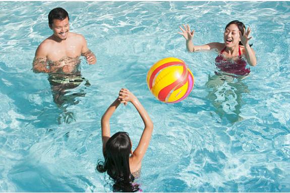 parents qui jouent au ballon avec leur enfant dans une piscine