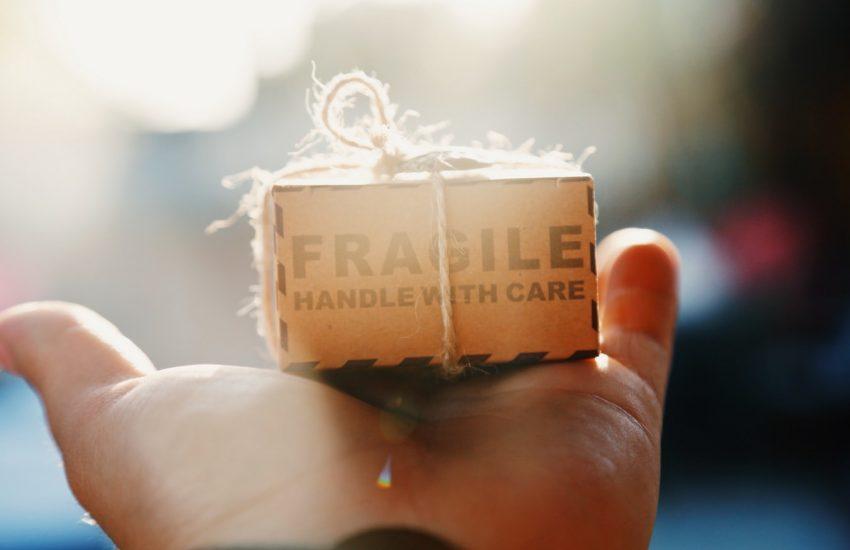 Personne qui tient un carton avec la mention fragile dans sa main pendant un déménagement