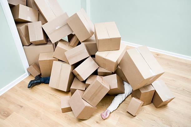 Personne ensevelie sous les cartons de déménagement après une chute