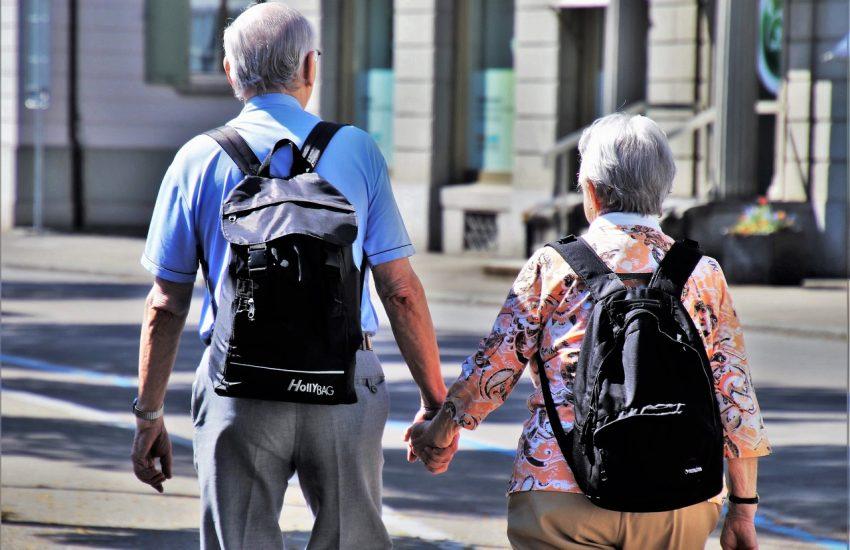 deux personnes agées de dos avec des sacs à dos se tenant la main