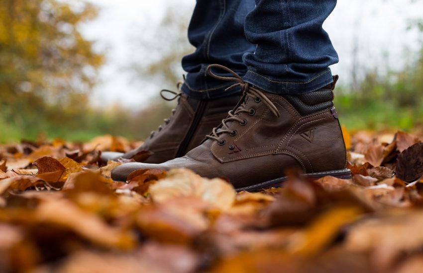 zoom sur les pieds d'un homme portant des bottines marron sur sol recouvert de feuilles mortes