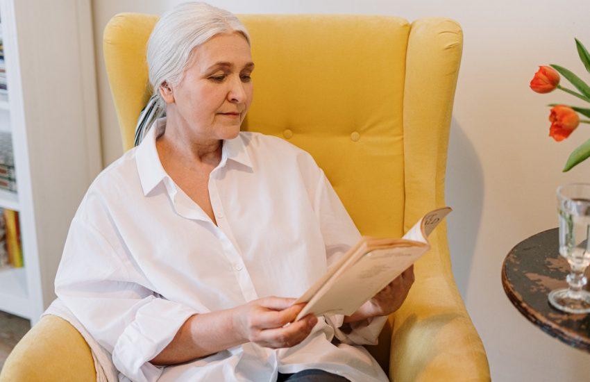 femme âgée assise dans un fauteuil jaune